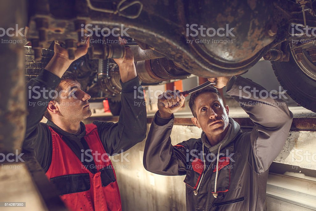 Mechanics working together on a chassis of a car. stock photo