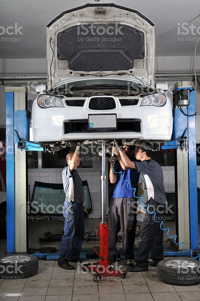 Mechanics working under a car stock photo