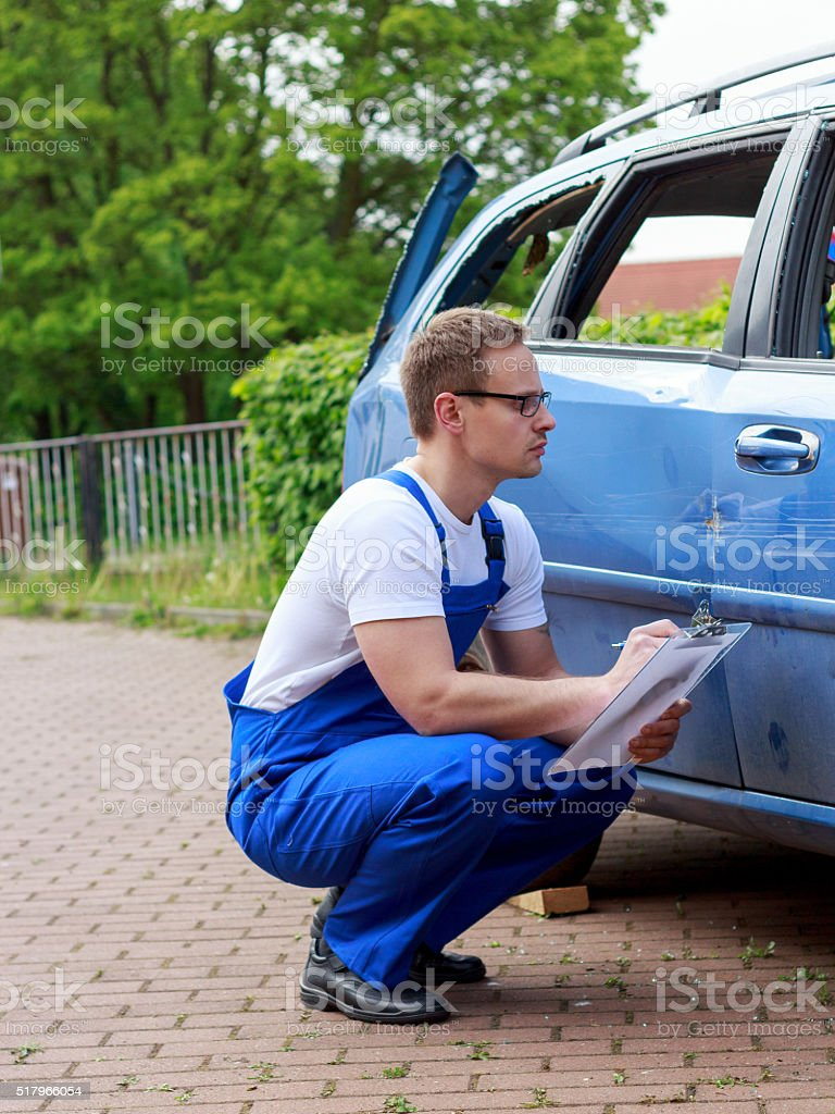 Mechaniker überprüft schaden am Fahrzeug stock photo