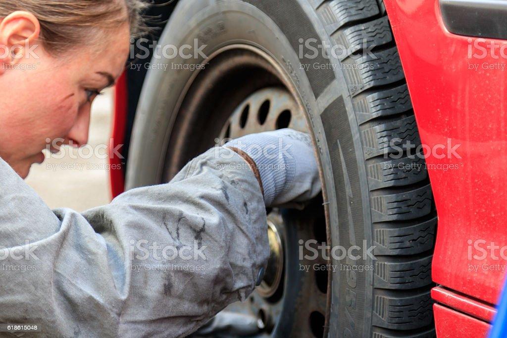 Mechanikerin wechselt Autoreifen stock photo