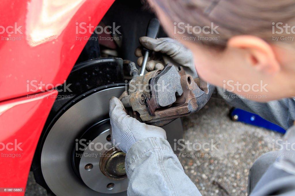 Mechanikerin wechselt Bremsen stock photo
