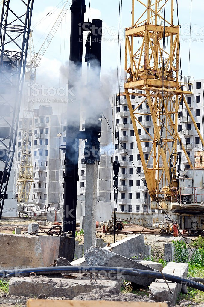 Mechanism scores piles at construction site stock photo