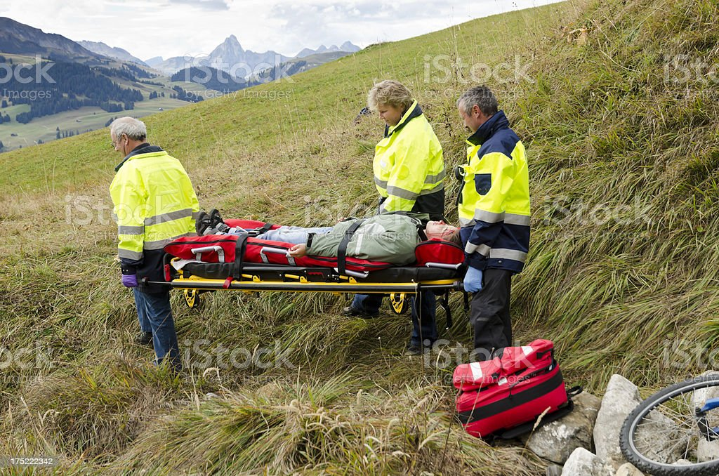 Medevac workers are carrying a crashed mountain biker stock photo