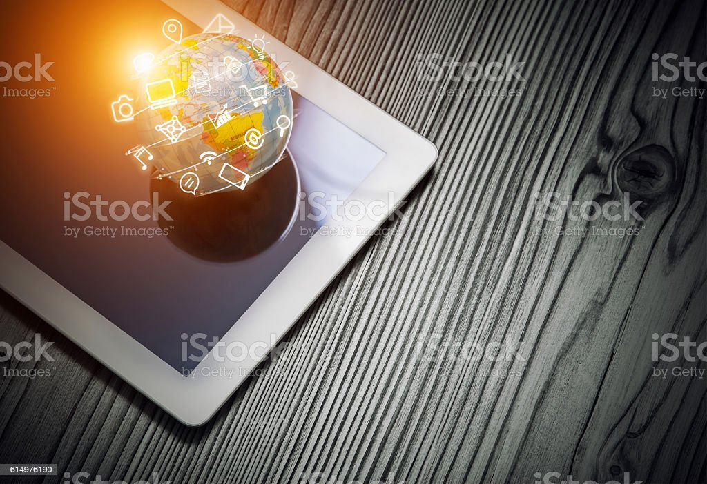 media app icons flying around globe on tablet computer stock photo