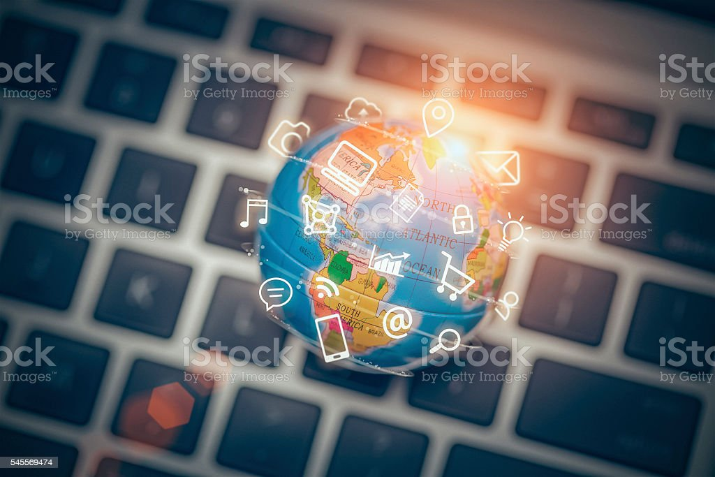 media icons fly off around globe on laptop stock photo