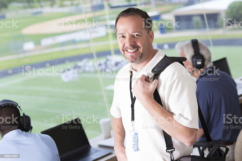 Media member arriving in press box at football game stock photo