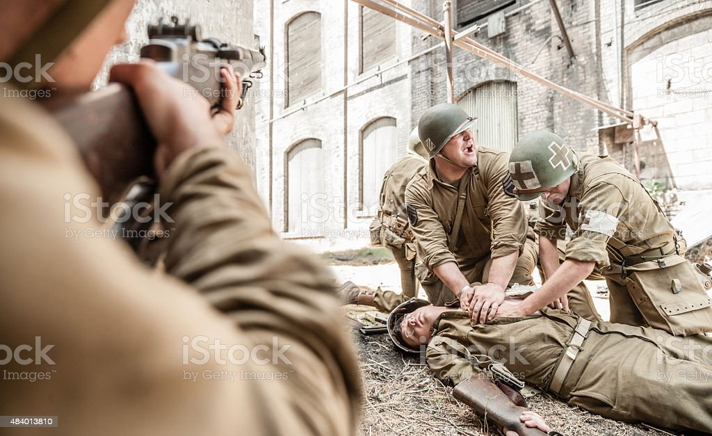 WWII Medic Administering First Aid to Wounded Soldier in Battle stock photo