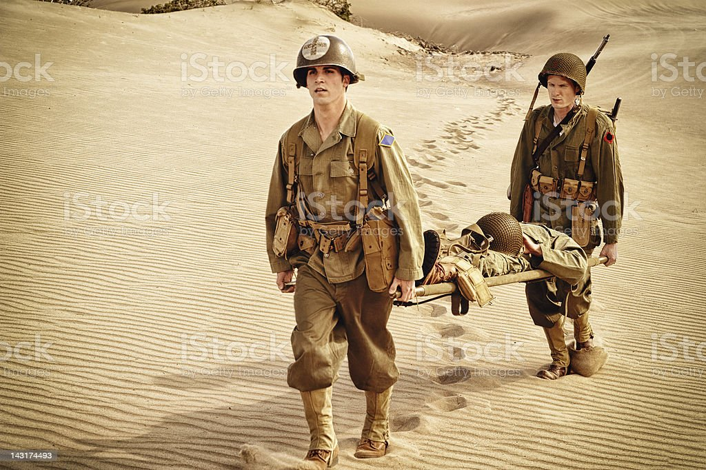 WWII Medic and Soldier Evacuating Wounded Man On Litter stock photo