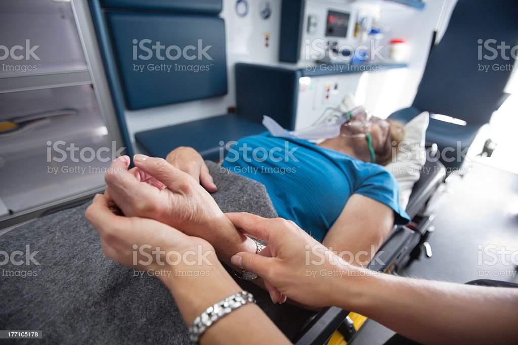 Medic measures a woman's pulse in an ambulance royalty-free stock photo