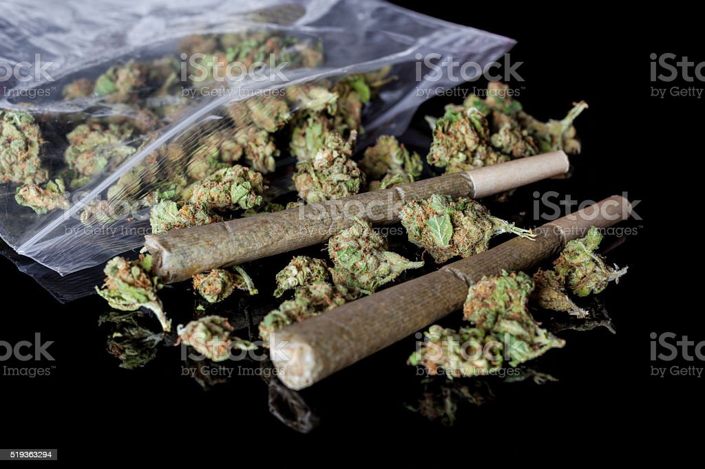 Medical cannabis joints and buds scattered from package black side stock photo