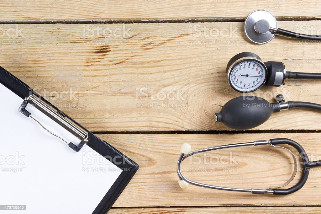Medical clipboard and stethoscope on wooden desk background. Top view. stock photo