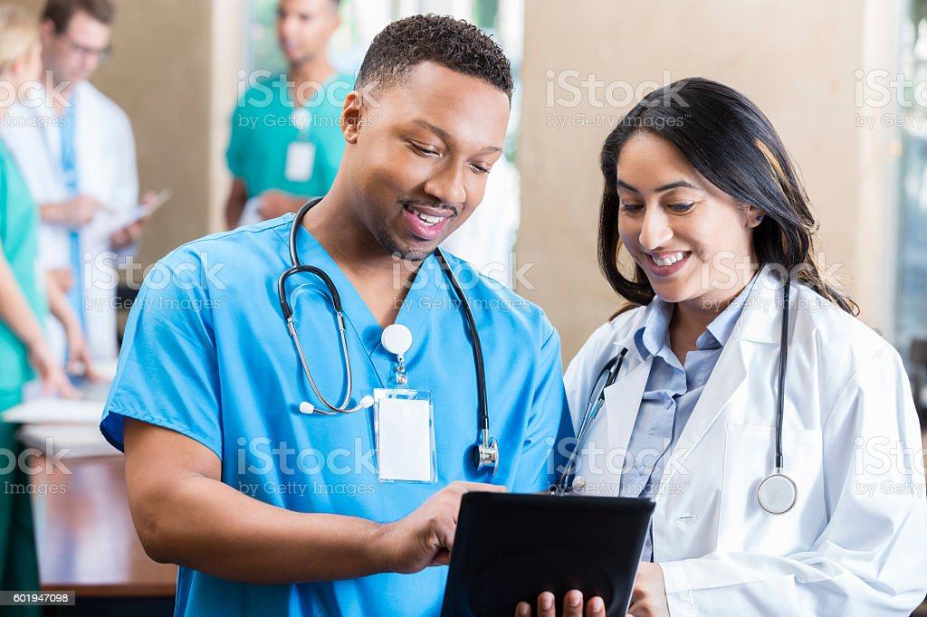 Medical colleagues look at something on a digital tablet stock photo