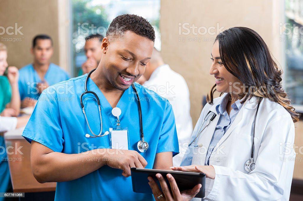Medical colleagues talk prior to hospital staff meeting stock photo