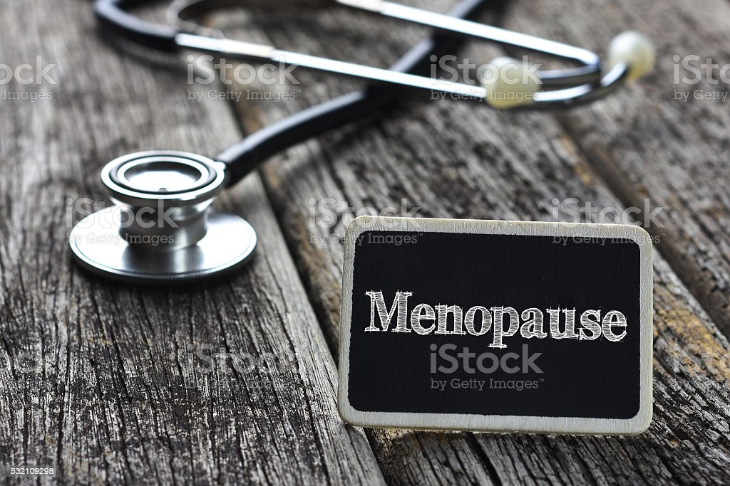 Medical Concept-Menopause word written on blackboard with Stetho stock photo