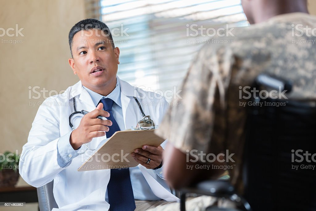 Medical doctor evaluates veteran during appointment stock photo