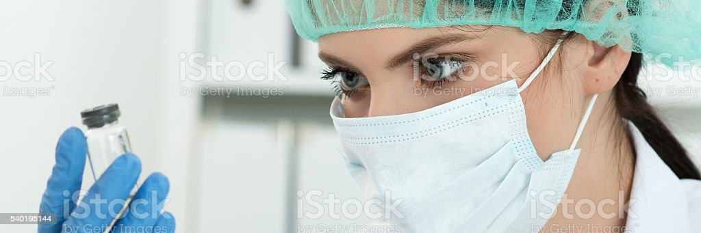 Medical doctor looking at small flask with liquid stock photo