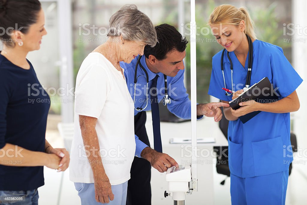 medical doctor monitoring senior patient's weight stock photo