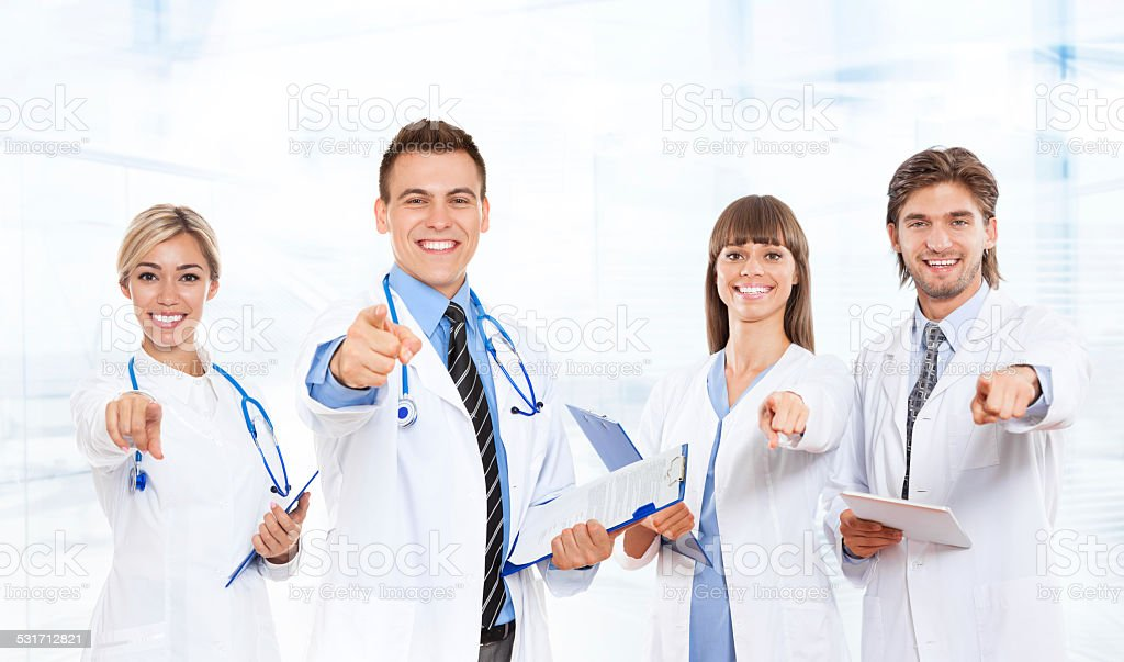 medical doctor team smile with stethoscope point finger at you stock photo
