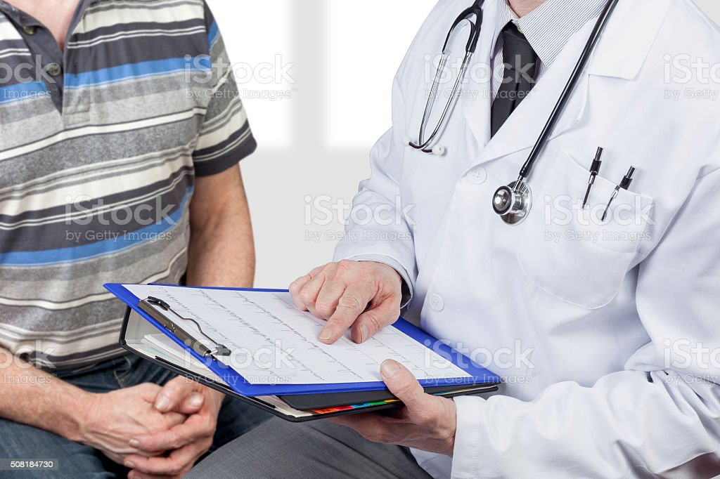 Medical doctor wearing stethoscope checking chart with patient stock photo