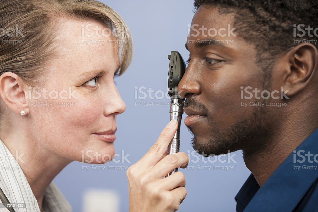 Medical Exam: Doctor Looks at Patients Eyes royalty-free stock photo