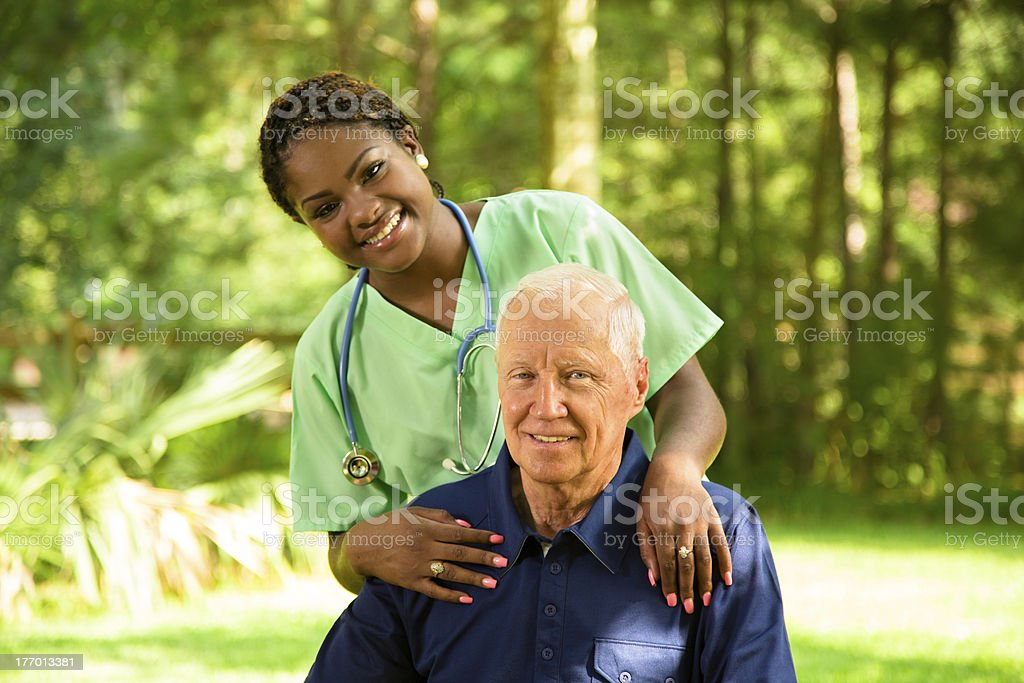 Medical:  Happy Caregiver visiting with senior man sitting outside. royalty-free stock photo