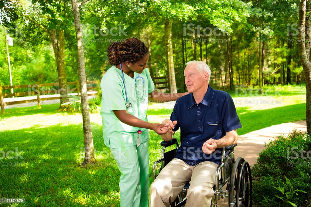 Medical:  Happy caregiver with senior man in wheelchair. royalty-free stock photo