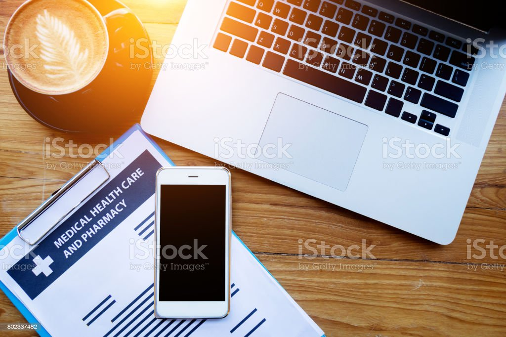 medical health care insurance online concept : medical health care policy document on clipboard with laptop and blank screen mobile phone on table stock photo