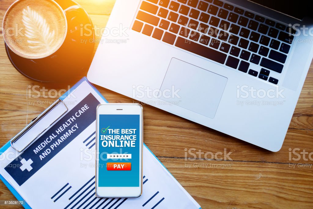 medical health care insurance online concept : medical health care policy document on clipboard with laptop and insurance online screen on mobile phone. Website ,application for apply insurance online stock photo