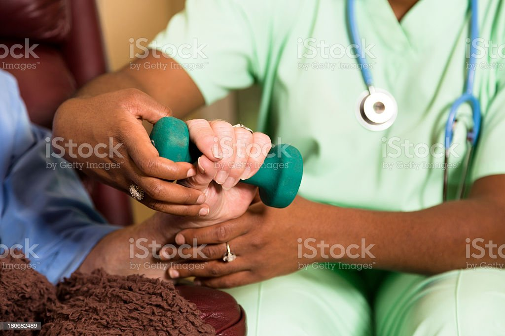 Medical:  Home healthcare nurse helping woman exercise after wrist surgery. royalty-free stock photo