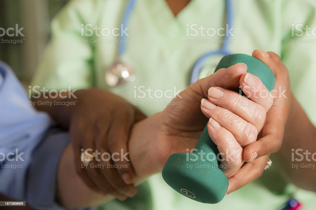 Medical:  Home healthcare nurse helping woman exercise after wrist surgery. stock photo