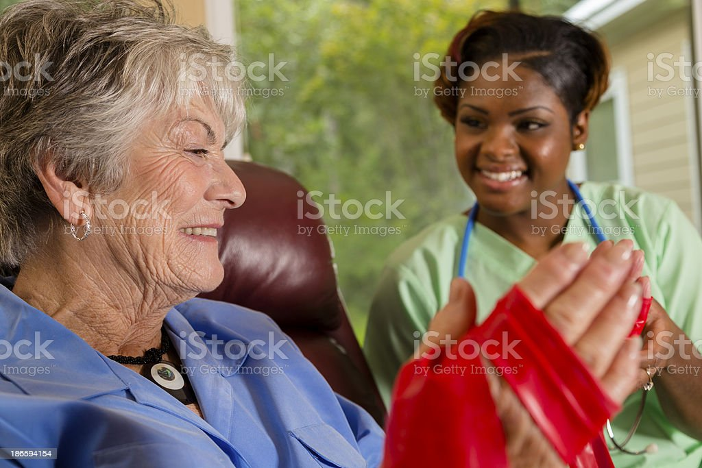 Medical:  Home healthcare nurse helps woman with band therapy. royalty-free stock photo