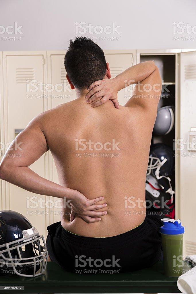 Medical: Male athlete massaging neck and back, football locker room. royalty-free stock photo