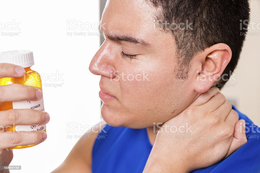 Medical: Male athlete massaging neck in pain, holding medicine bottle. royalty-free stock photo