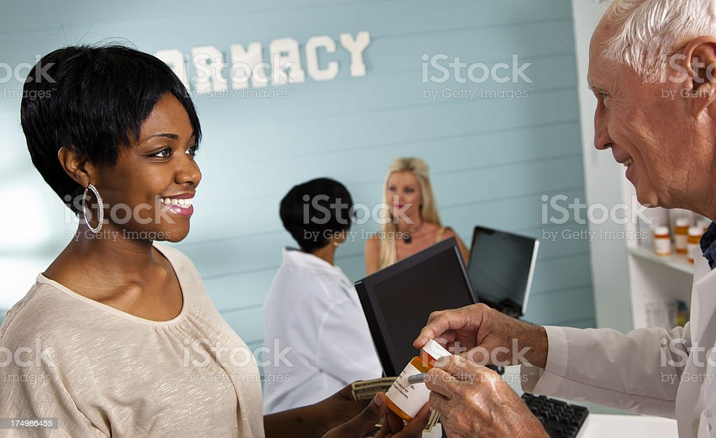Medical: Pharmacist assisting customer. Co-worker in background also helping. royalty-free stock photo