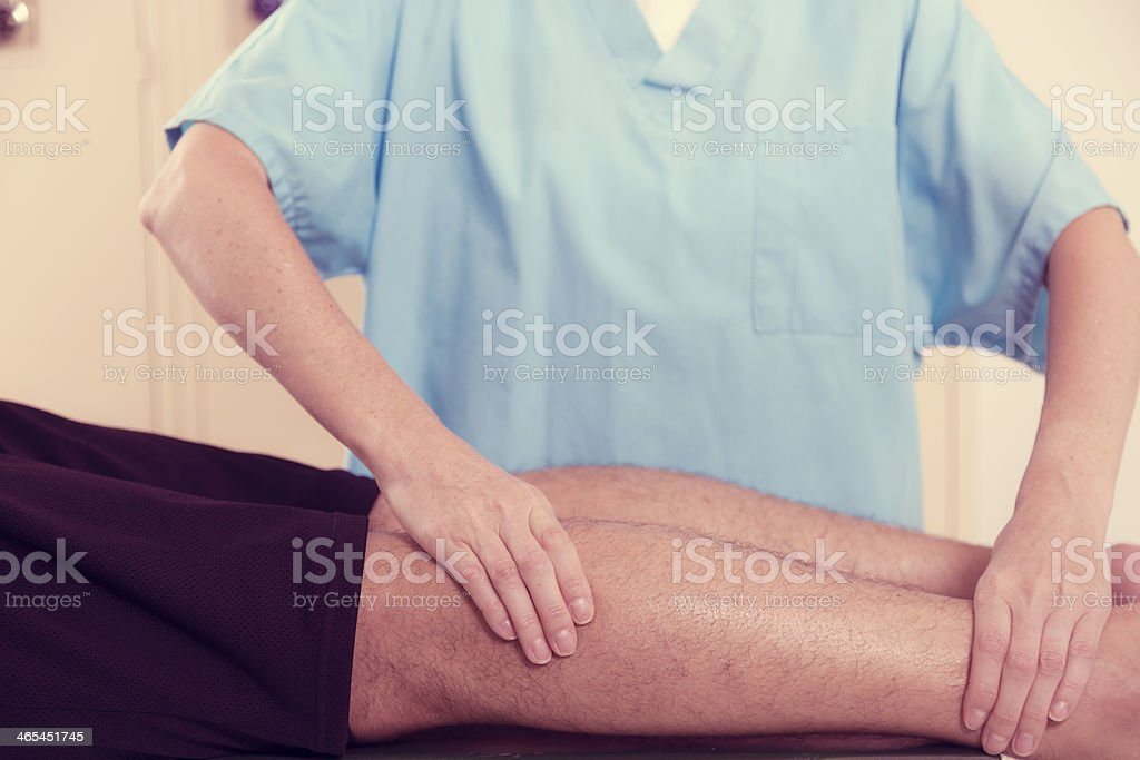 Medical: Physical therapist, male athlete in locker room. Injury. stock photo