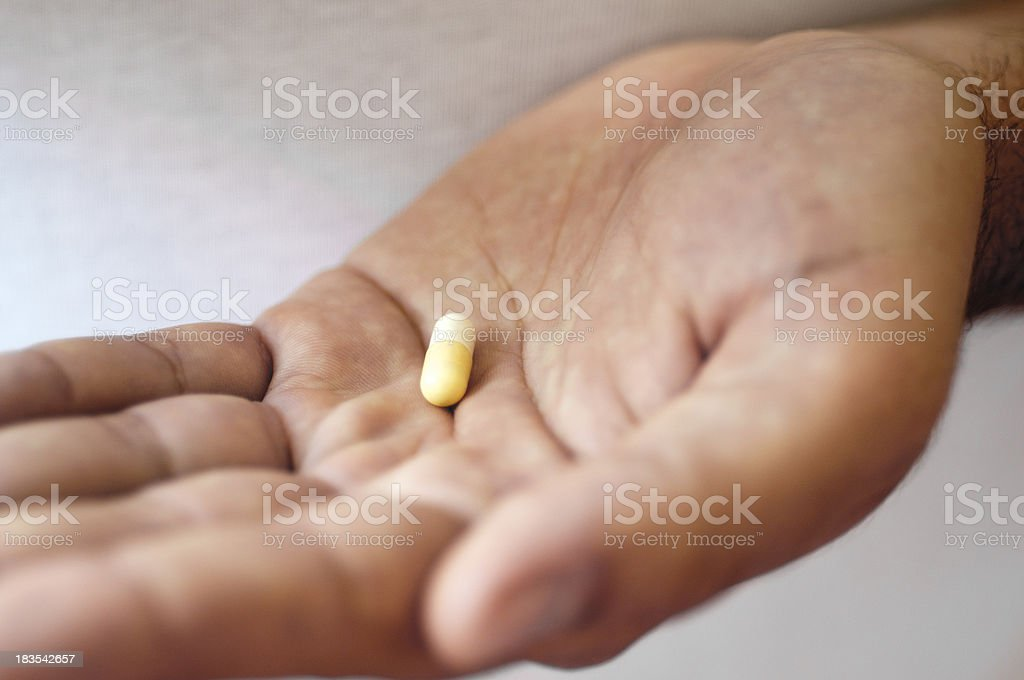 Medical pill in hand, close-up stock photo