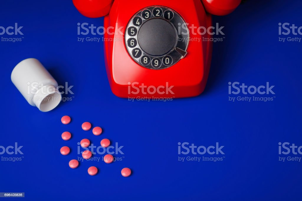 medical pills  and red telephone blue background stock photo