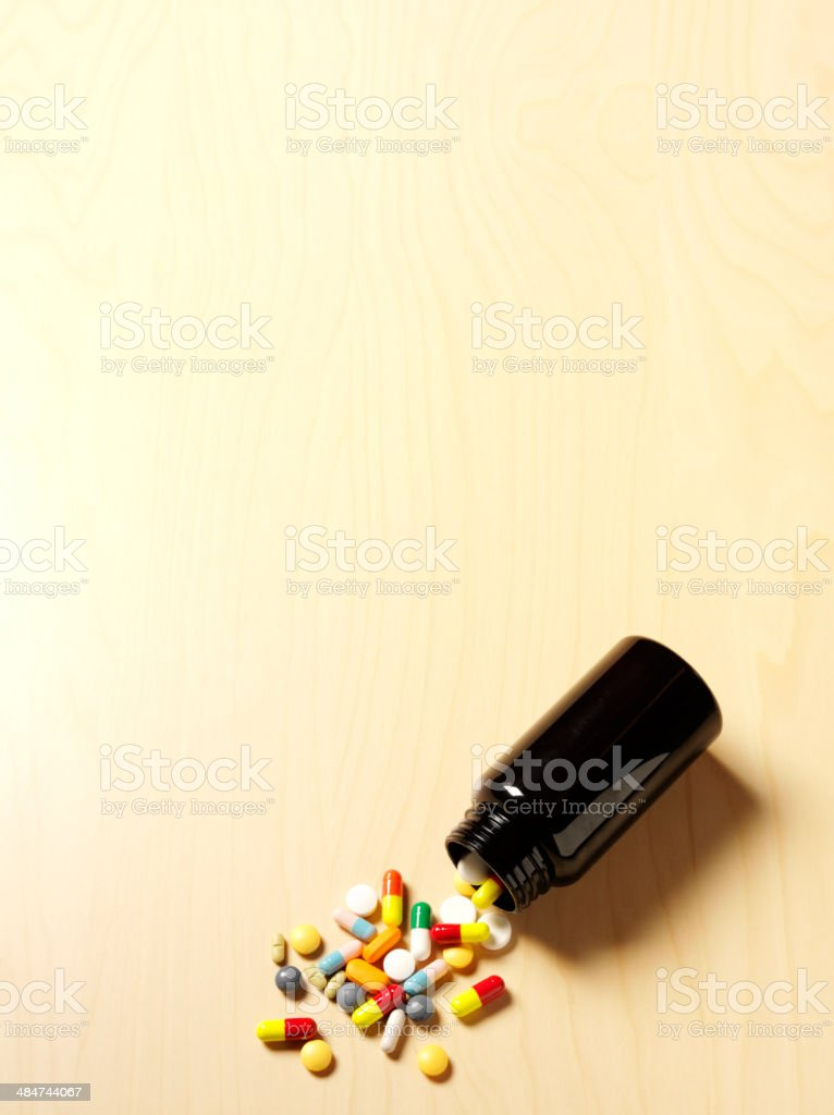 Medical Pills Spilling from a Bottle onto a Wooden Desk stock photo