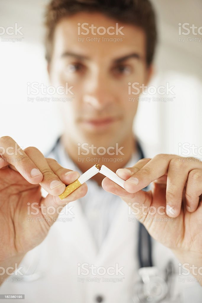 Medical practitioner breaking a cigarette royalty-free stock photo