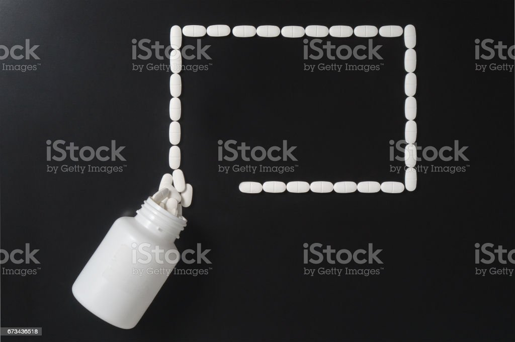 Medical presentation background with a lot a free empty copy space for your text. Pills spilling out from bottle and forming a rectangle. stock photo