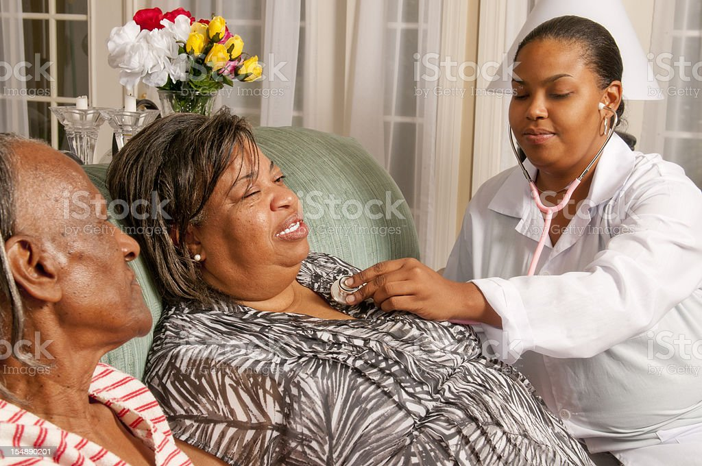 Medical Procedure in Home of African American Women royalty-free stock photo
