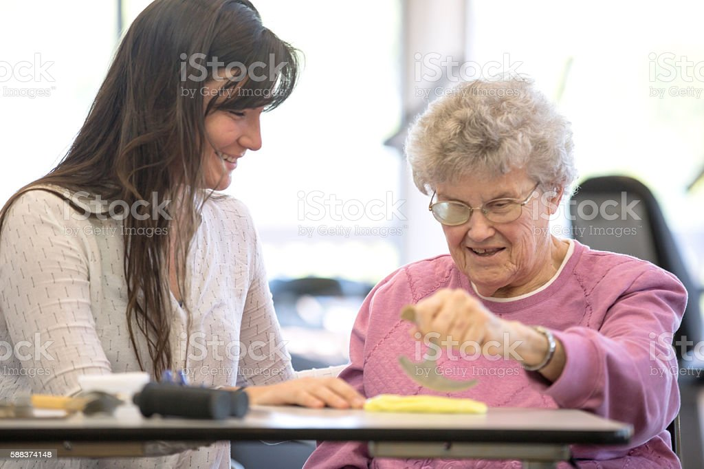 Medical professional and elderly woman smiling during physical therapy stock photo