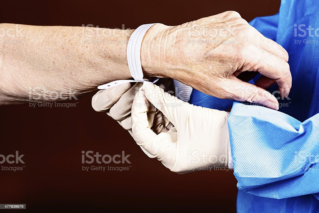 Medical professional attaches hospital identity bracelet to elderly arm stock photo