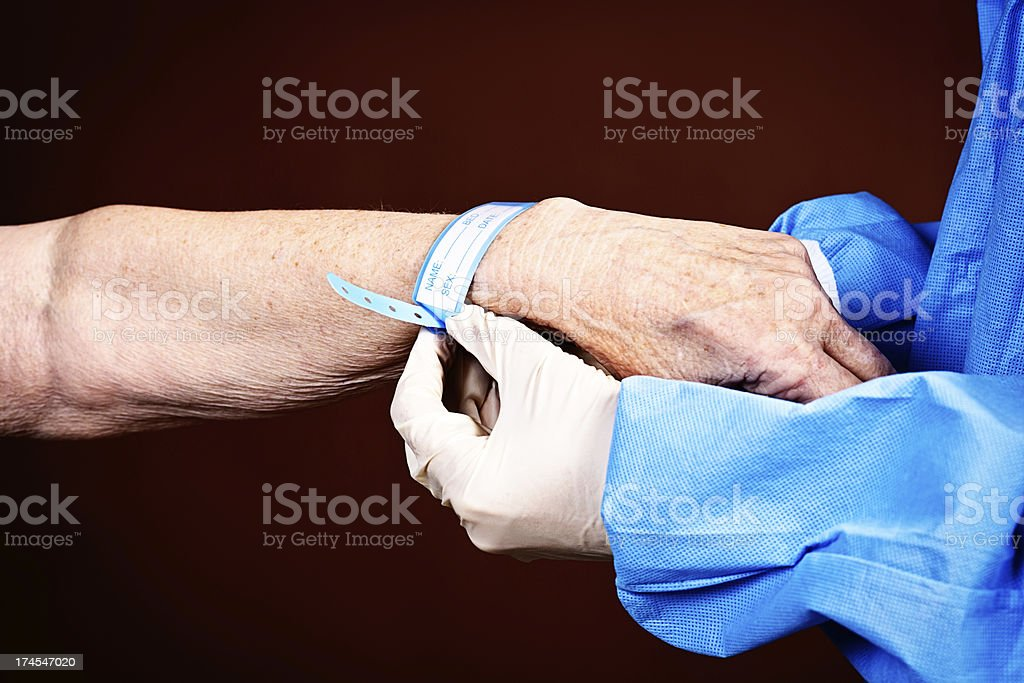 Medical professional fastens hospital ID tag on old arm stock photo