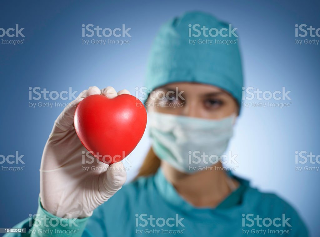 Medical professional on scrubs holding up red heart stock photo
