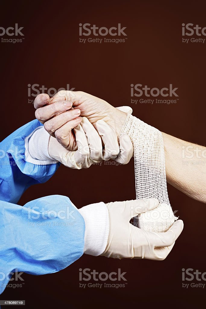 Medical professional puts surgical dressing on female arm royalty-free stock photo