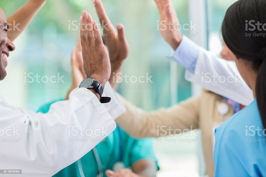 Medical professionals give high fives stock photo