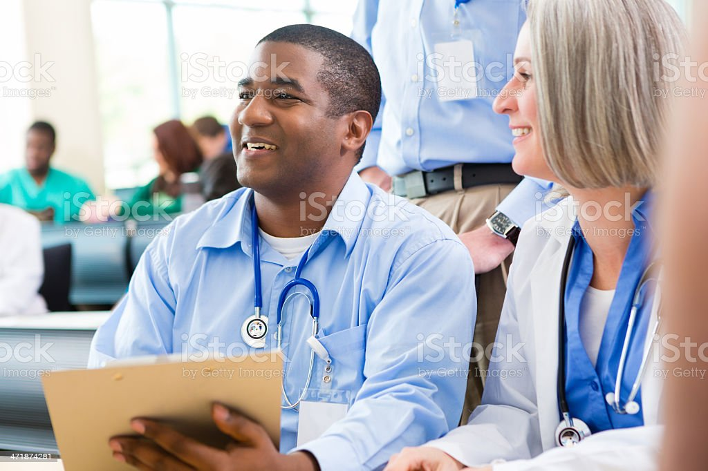 Medical professors helping students sign up for seminar or lecture stock photo