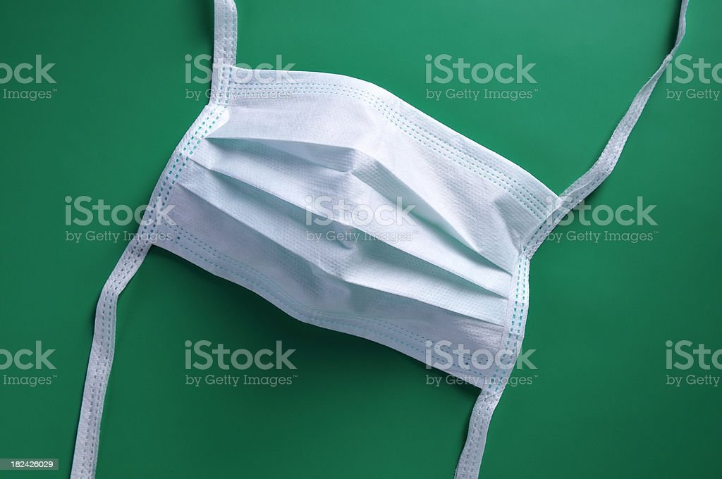 Medical protective mask on green background stock photo