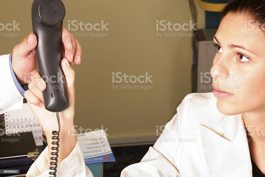 Medical secretary handing a phone to the doctor royalty-free stock photo
